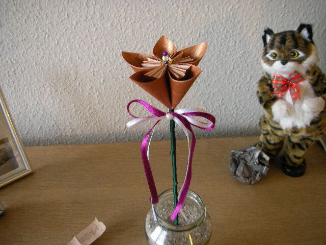 copperflower on a stick wrapped with silkribbon. added a double bow also silkribbon and a pin with pearls in center of flower