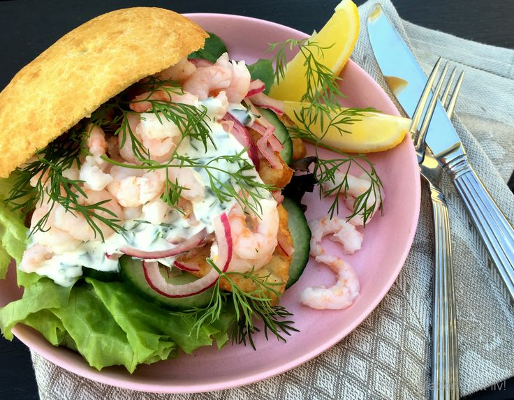 Lækker fiskeburger med rødspættefileter og rejer - serveret med masser af grønt og en cremet dressing med friskhakkede krydderurter