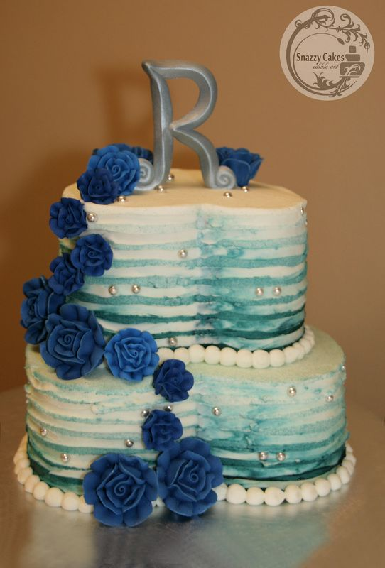 heart shaped cake with blue watercolor effect on buttercream and blue royal icing roses