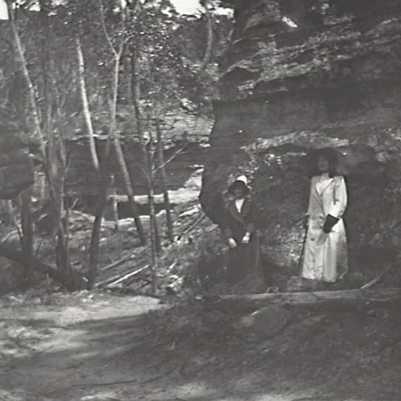 Title: Old Western Road, Mt. York Date & Location: 27 October 1912, 	 Blue Mountains (NSW); Mount York (NSW) Description: Black and white glass lantern slide. Title in ink on upper edge label 	 Section of old Western Road through bush at Mount York, with two unidentified women standing roadside in the shade of the rockface. From negative in Mitchell Library Frank Walker Collection ON 150, Item 992.
