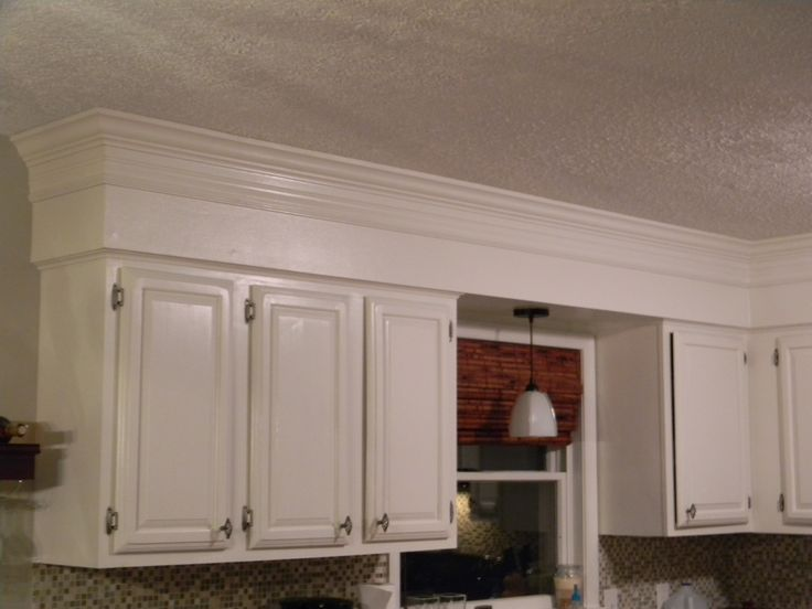 Have 80's bulkheads in your kitchen? Not anymore! Make your old cabinets look like custom-to-the-ceiling cabinetry by adding some crown molding and painting the bulkhead and old cabinets to match.