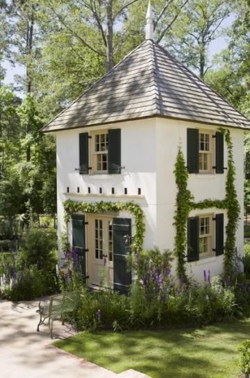 This gorgeous, two-story playhouse was built in the same style ast the main house - vines and all - so it blends in beautifully! | 14 fun treehouses and playhouses | Living the Country Life | http://www.livingthecountrylife.com/buildings-fences/outdoor-ideas/14-fun-treehouses-and-playhouses/