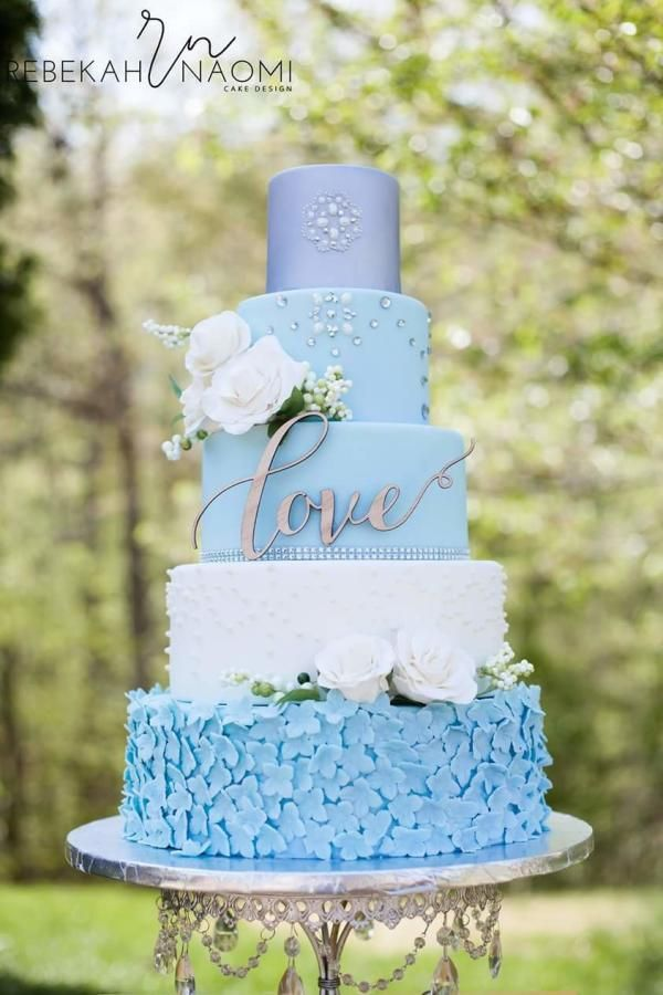A beautiful five tier wedding cake in blue, white and silver with edible pearls, sugar roses and hydrangea.