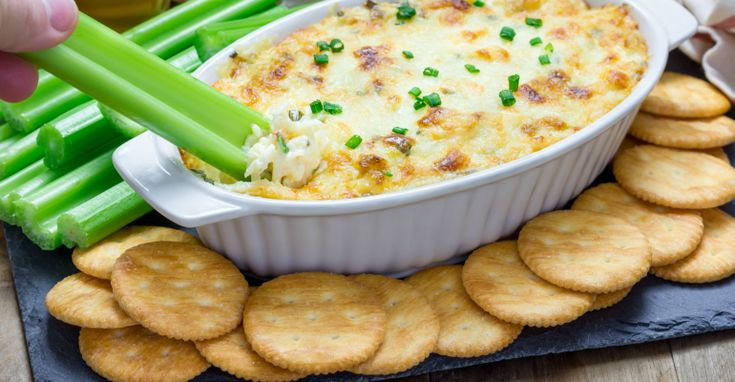 Old Bay baked crab dip sitting in a white dish with celery and crackers surrounding it. A hand dips a celery stalk into the crab dip.