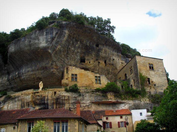 Les Eyzies-de-Tayac-Sireuil: Falaise, statue, ancien château abritant le musée National de Préhistoire et maisons du village, en Périgord - France-Voyage.com