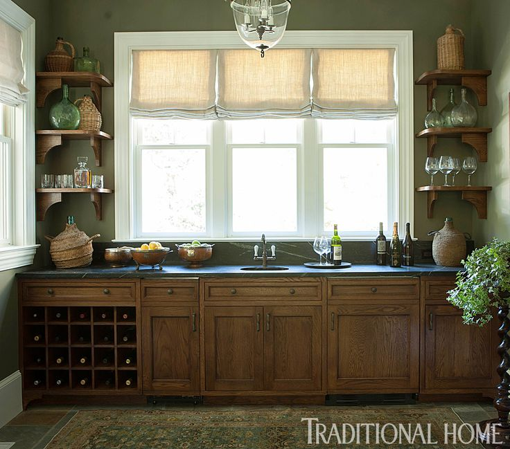 beautiful stained oak cabinets with a sopastone counter provide ample prep space at the bar