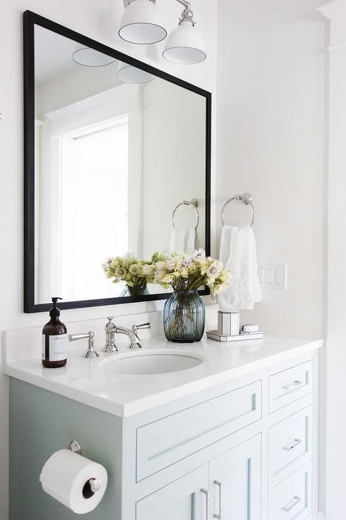 Lit by a white two light sconce, a pale blue vanity painted Benjamin Moore Woodlawn Blue is accented with a white quartz countertop holding a round sink with a polished nickel faucet kit beneath a black mirror mounted on a white wall beside a polished nickel towel ring.