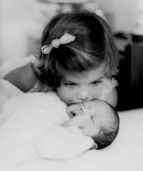 Caroline Kennedy, kissing her baby brother John F. Kennedy Jr. in 1961 in Palm Beach, Florida. Richard Avedon