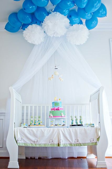 like the idea! i have a crib that would work too. instead of tule, attach paper raindrops to pom poms. minus the balloons