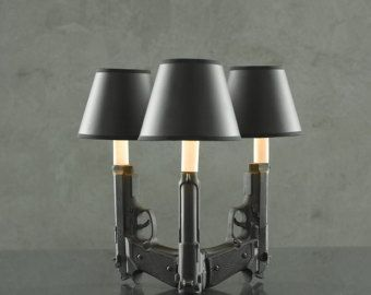 ***Priced individually***  These are handmade ceramic lamps. Each 9mm is slip-cast in ceramic using plaster molds and reproduced to create these sconces. The actual Gun measure 4 x 7 (in height), with a 4 shade and fixture the total height is about 13.  Each sconce comes with a 40 watt candelabra bulb and a matte black top hat shade that is lined with gold for a beautiful luminance of light. Theyre wired with 8 of cord and a plug ready to light up your room. Most often there is about a 3-5…