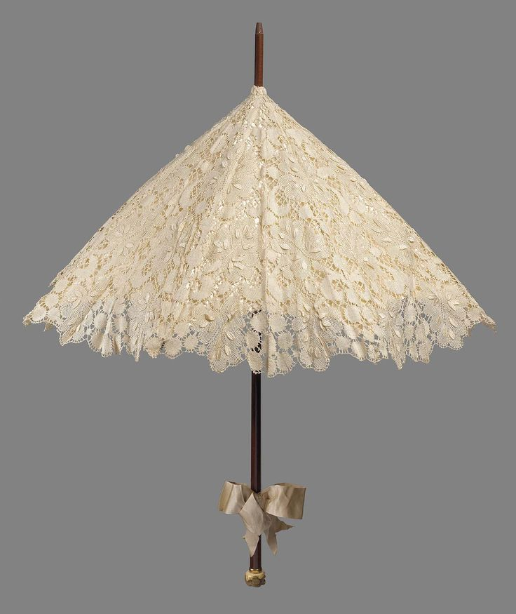 Cream colored silk bobbin lace parasol in heavy symetrical design of ornamental leaves, lined with cream colored satin bow tied on plain brown wooden handle, knob of carved ivory with monkey picking fruit at end ofhandle.