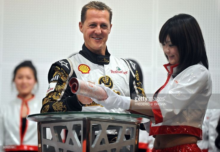 Seven-times F1 world champion Michael Schumacher signs a replica of the 2008 Olympic Torch in Beijing on November 3, 2009. Beijing's iconic Bird's Nest Stadium has been turned into a motor racing track with the world's top drivers gearing up to compete 2009 Race of Champions. AFP PHOTO/Frederic J. BROWN