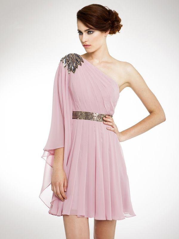 Precioso vestido de gasa, con esocte asimétrico y con una manga, cuerpo y falda de tablas, decorado por un cinturón en lentejuelas y un flor a la altura del hombro también de lentejuelas.
