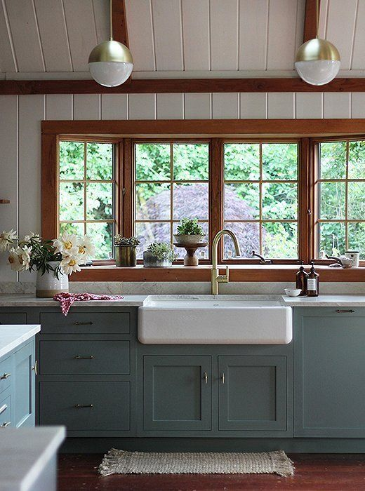 Beautiful rustic country kitchen with shiplap walls, brass hardware, and painted French blue cabinets.