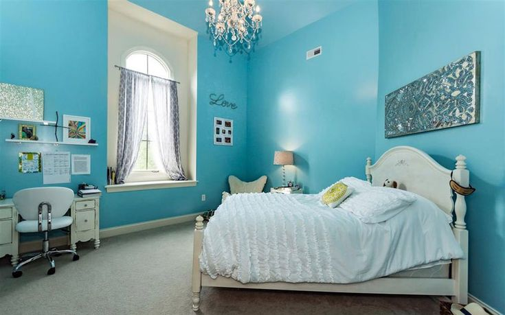Teal painted room with high ceiling and chandelier