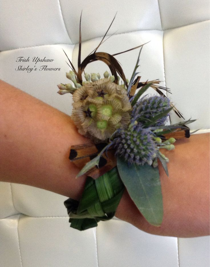Wrist corsage of lily grass weave scabiosa pod, thistle and pheasant feathers.