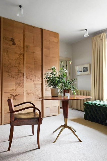 Laser-etched cupboards in Clothes storage ideas. Large white dressing room with built-in wooden cupboard, mid century furniture and cream curtains.