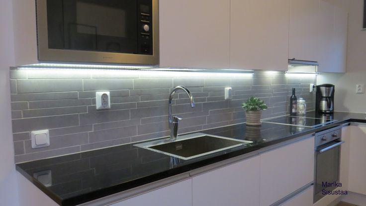 Moderni mustavalkoinen, valkoinen keittiö. Musta kivitaso, harmaa