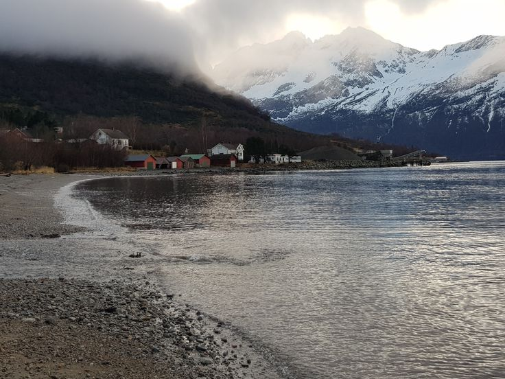Strand i Norge. I bakgrunnen skyer som har dekket fjellet. Beach in Norway. In the background you see clouds covering the mountain.