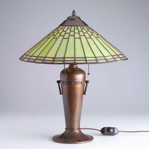 "ROYCROFT Rare hammered copper table lamp designed by Dard Hunter with a flaring leaded glass shade of bright green and purple panels over a baluster three-socket base with two riveted rings and handles. Original dark patina to base, excellent new patina to heat cap, a couple of short breaks to smaller squares. Unmarked. 22 1/2"" x 18"""