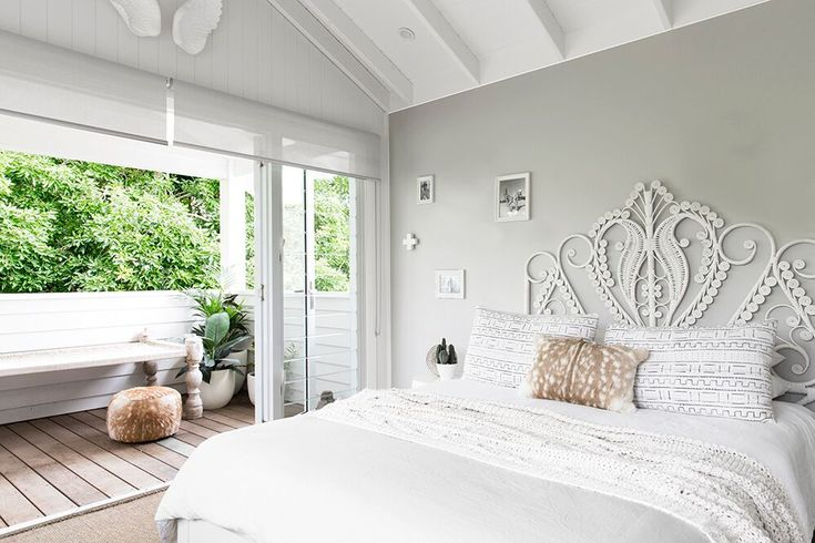 A sweet young girls bedroom with neutral linen tones, white cane bed head on a soft grey wall, under raked ceilings. The Grove Byron Bay