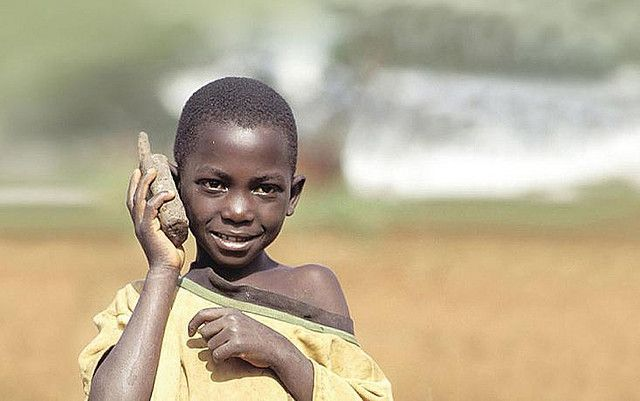 African boy holding a fake wooden cellphone up to his ear.