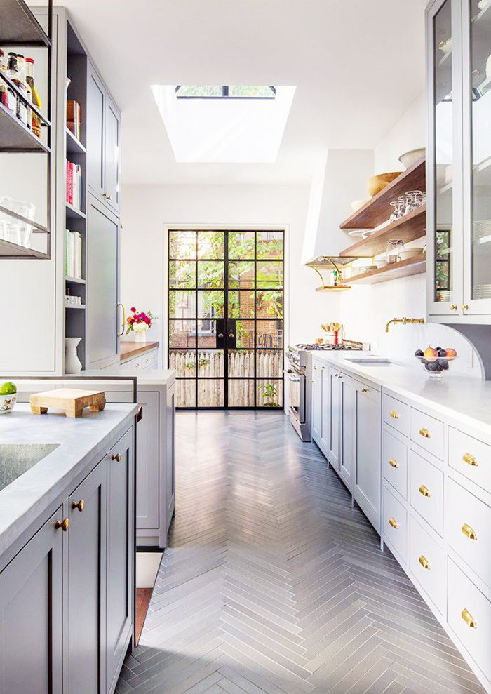 Kitchen with white walls, white cabinets, wooden shelves, and a glass door