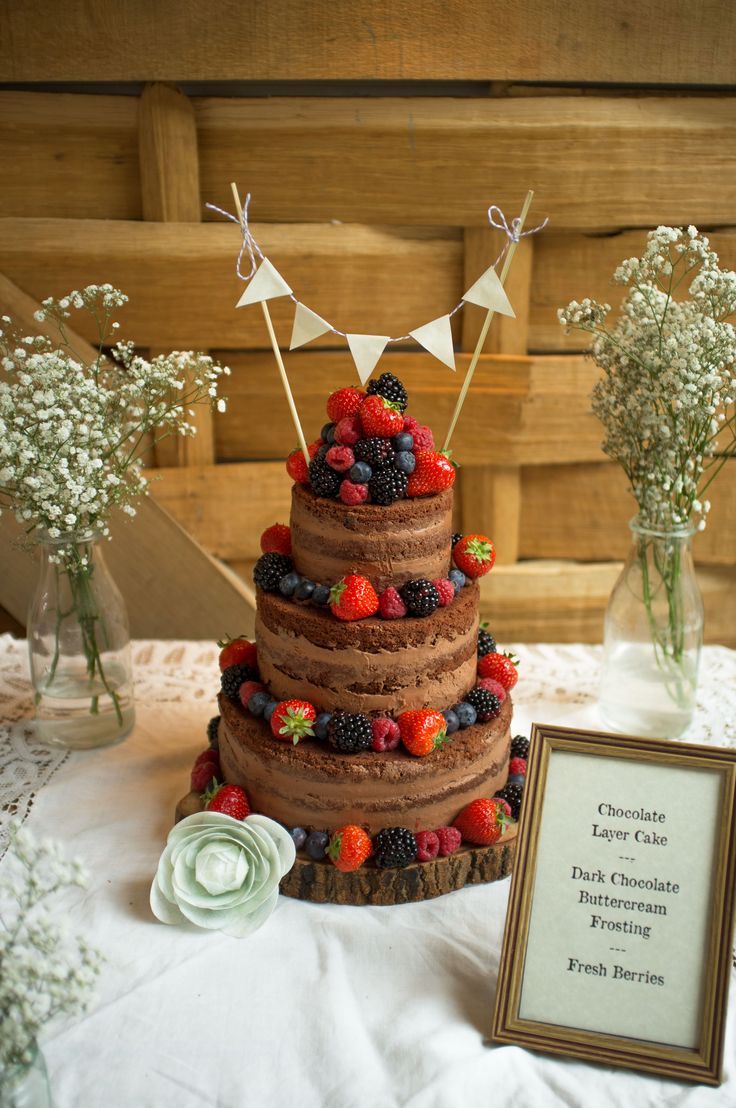 Chocolate naked wedding cake. Naked cake. With fresh berries by…