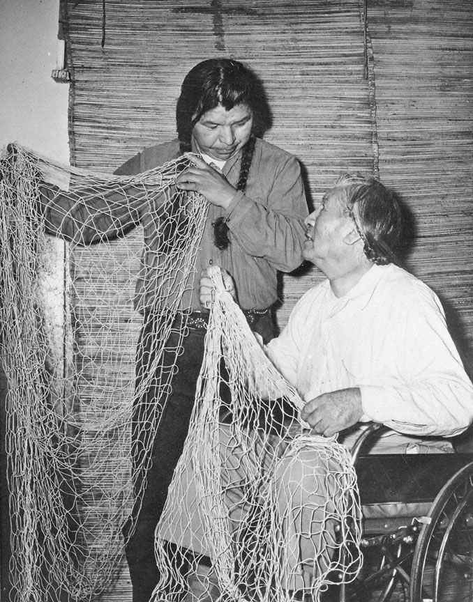 This photo shows Celilo Village residents Jimmy George, left, and Charley Quittoken, right, holding up fishing nets once used to catch salmon at Celilo Falls. Netmaking has long been an important art among Columbia River Indians, who have relied on the river's abundant salmon runs for millennia. Columbia River Indians traditionally made many different kinds of nets to catch salmon and other fish. The two nets shown above are dipnets, the most commonly used net at Celilo Falls prior to the…