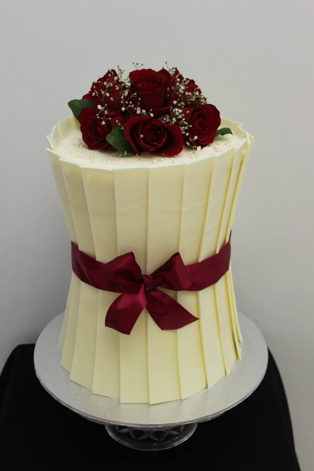 A romantic barrel shaped chocolate shard cake with red roses