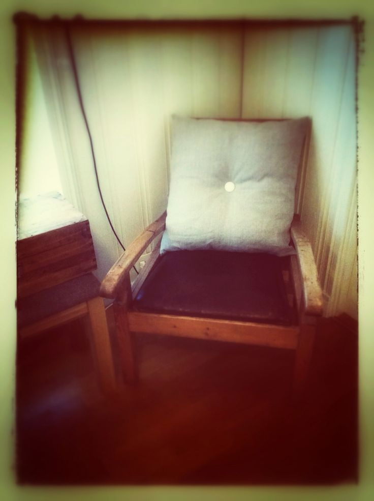 Farmchair with leather seat and linen cushion.