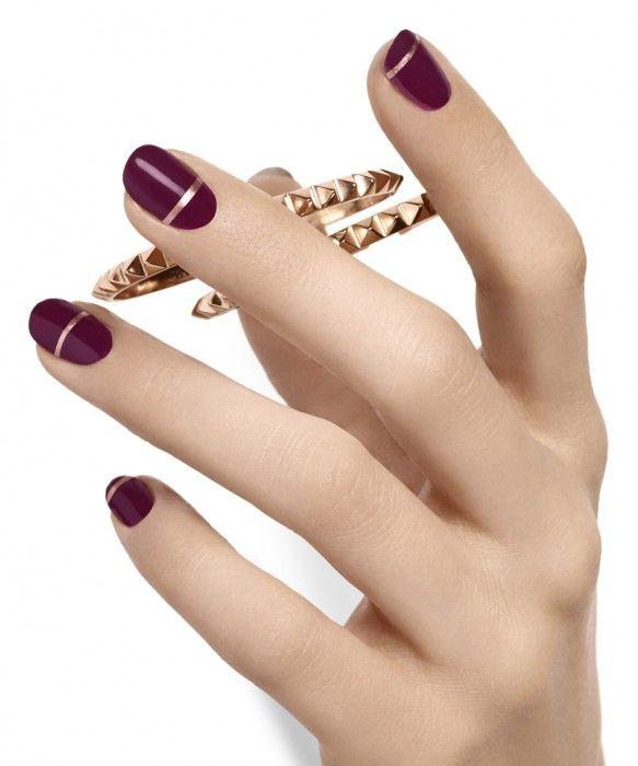 Uñas de color ciruela con lineas doradas