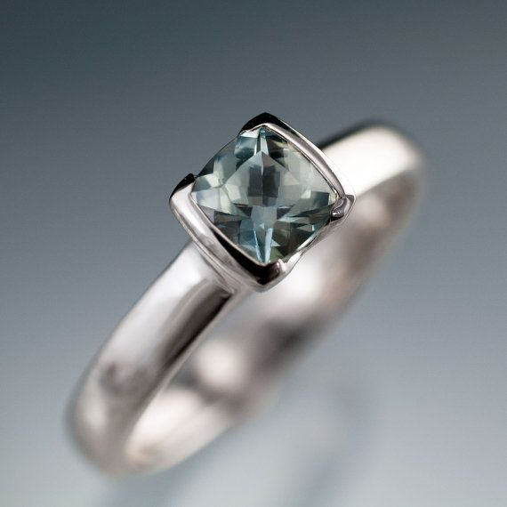 A cushion cut green-blue sapphire set in a half bezel setting in this elegant engagement ring. The solitaire setting grows seamlessly out of the slightly rounded ring shank. The setting is a modified bezel setting with a low cut on 2 sides. It protects the gem stone and holds it securely while allowing light to enter from the sides to ring out more of the amazing sapphire.
