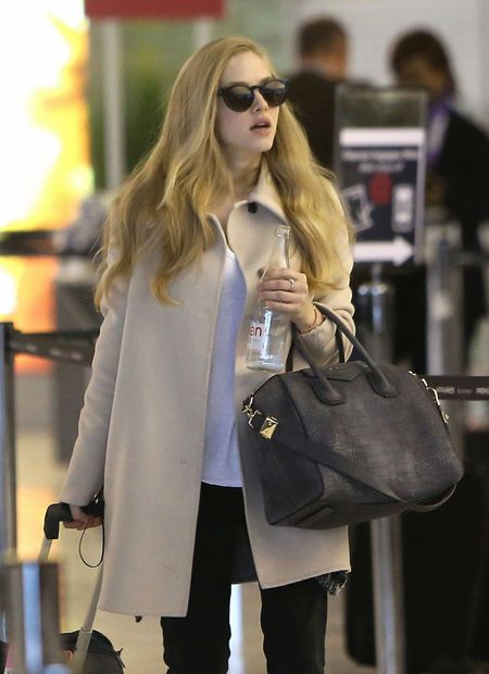 Amanda Seyfried at Roissey Airport in Paris looking luminous and glamorous to levels not normally associated with pre- or post-flight states.