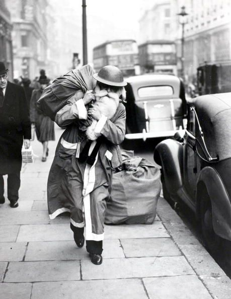 World War Two: 23rd December 1940, Father Christmas walks the streets of wartime London, The old man has exchanged his civilian red hood for a warlike 'tin hat', but, blitz or no blitz, he is delivering goods this year ~