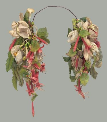 Woman's headdress, French, worn in Boston, mid-19th century. MFA, 52.1262. Woman's headdress; band of wire covered in reddish-brown cloth tape across top; bunches of artificial flowers and leaves at ends that consist of light pink blossoms and buds (possibly honey suckle), bright pink elongated blossoms and buds (possibly fuscia), elongated green and brown gauzy leaves and rounder leaves in the same material, shiny reddish-brown and light green berries.
