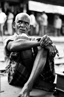 Emteaz Ahmed Epu: The photo was taken from The Chittagong Railway station at 12:40pm on 5th September 2013. Inthis photo, the man is an old cobbler. He has been doing this job during 12 years in the same place. He is the only wage earner in his family. His cautious looking making us that work is more welcome then talks.