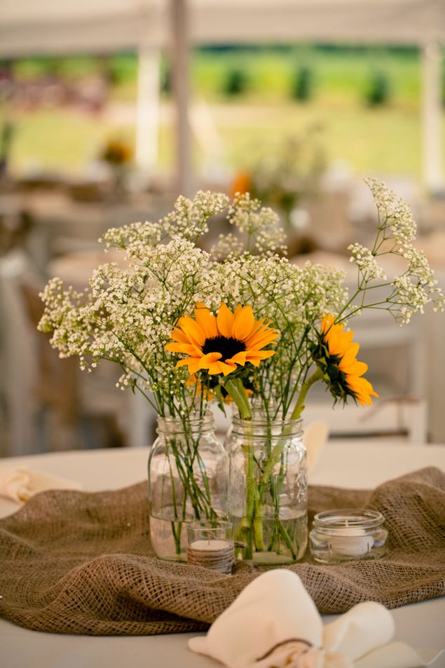 Mason jars, Burlap, Babys breath. #rusticweddings I like how the burlap is piled in the center of the table. Nice alternative to a runner!