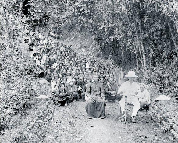 Koloniaal ambtenaar met inlandse bestuurder en arbeiders, ca. 1900