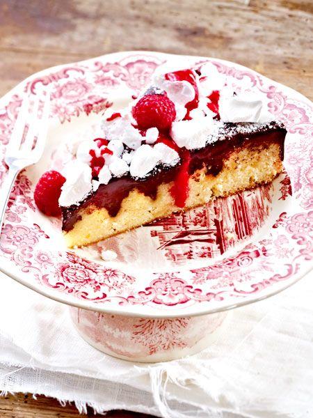 ... mit Baiser und Himbeersoße. Mit dem Kochlöffel wir der Kuchen übrigens gelöchert, damit die Schokosahne hineinlaufen und für ein schönes Muster sorgen kann.