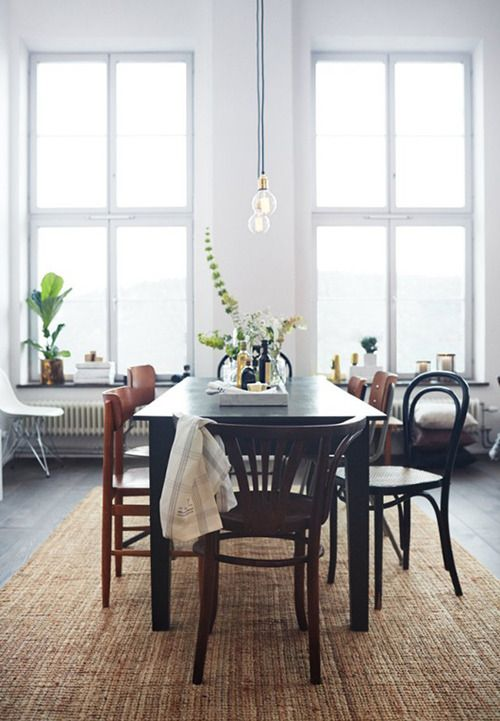Perfect dining space: lots of windows, streaming daylight, white walls, accents of greenery.