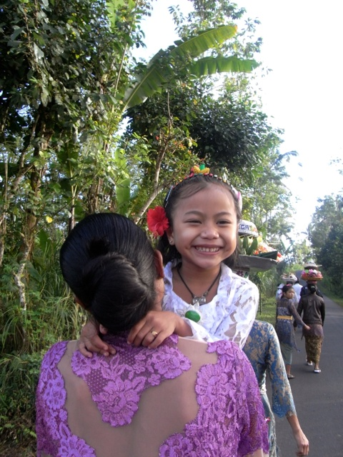Komang getting a lift from her mother for the 2km walk to temple