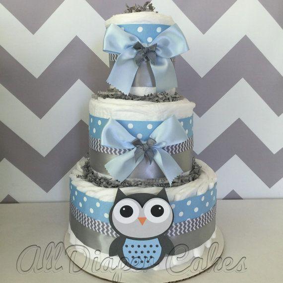 Ce gâteau de couches Owl Deluxe est construit de 3 couches de marque couches et rubans de haute qualité et noeuds. Décoré dans un schéma de couleur bleu et gris clair populaire. Ce 3 niveaux gâteau de couches serait faire la pièce maîtresse parfaite à la douche de bébé sur le thème à venir