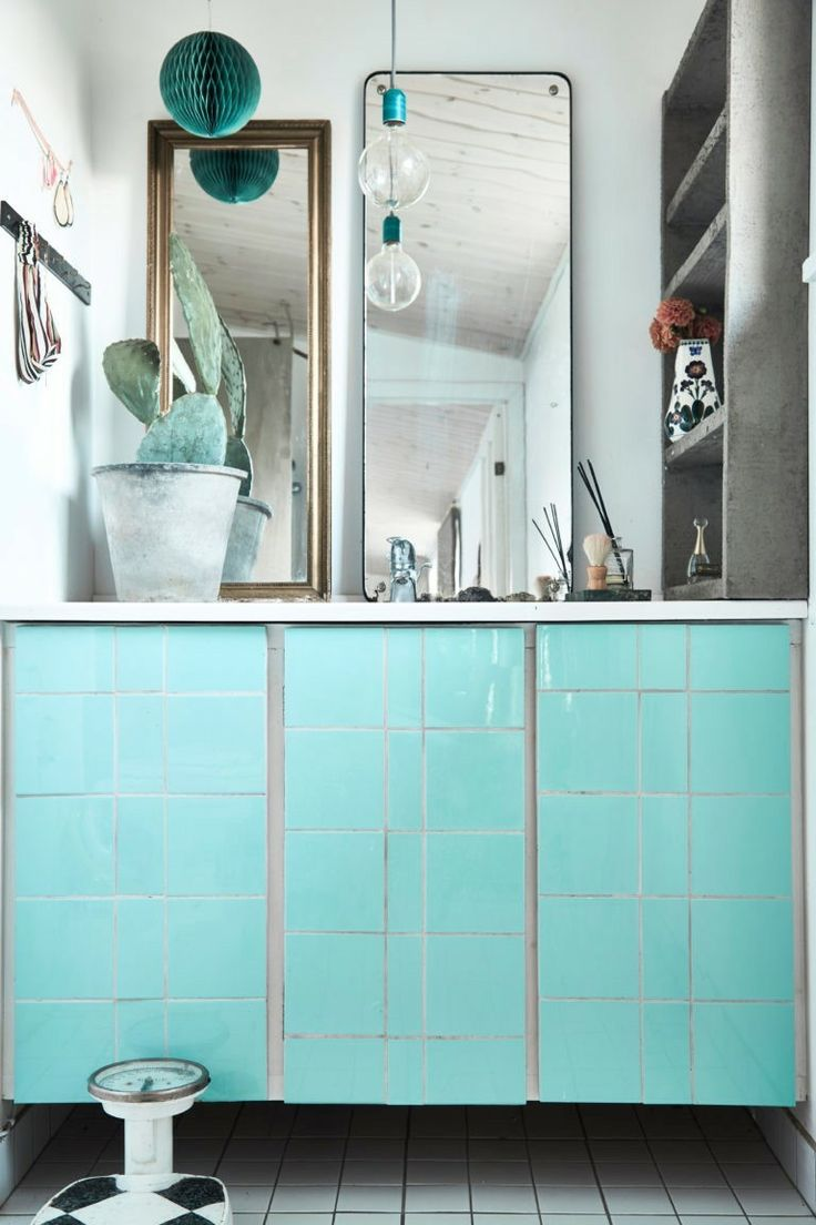 "In the bathroom, the sink console is clad in pale aqua tiles. ""I love colors, green and blue in particular,"" Cecilie Noer says. ""I feel about colors the same way I do about music."""