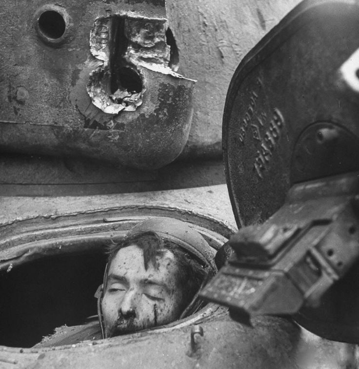 Cologne, Germany, March 6,1945: US tank driver Julian H. Patrick, still sitting in the driver's seat, is dead after suffering the effects of a direct hit from a German Panther during the Battle of the Cologne Cathedral. Note the hole in the tank's turret, above Patrick's head.The tank commander died in the turret, the gunner was seriously wounded but survived, and the asst driver exited from escape hatch and survived unharmed.