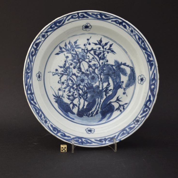 www.orientalceramics.com A Ming Blue and White porcelain dish made for the Japanese market, Tianqi or Chongzhen c.1620-1640. Decorated with the 'Three Friends of Winter', Pine, Bamboo and Prunus. The arrangement is somewhat unusual in that the plants are more intertwined than they are normally depicted. The cavetto has prunus flower-heads, the rim border has geometric scrolls with further prunus flower-heads.