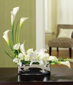 white calla lilies, white lisianthus, white roses, and white orchids are balanced against green trachelium and blades of flax....picture with purple orchids!