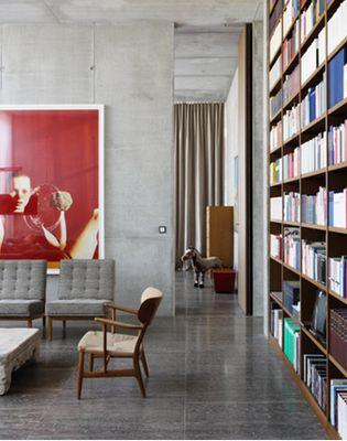 FULL HEIGHT TIMBER BOOKSHELF. POLISHED CONCRETE FLOOR. CEMENT RENDER WALLS. High ceilings. Red artwork.