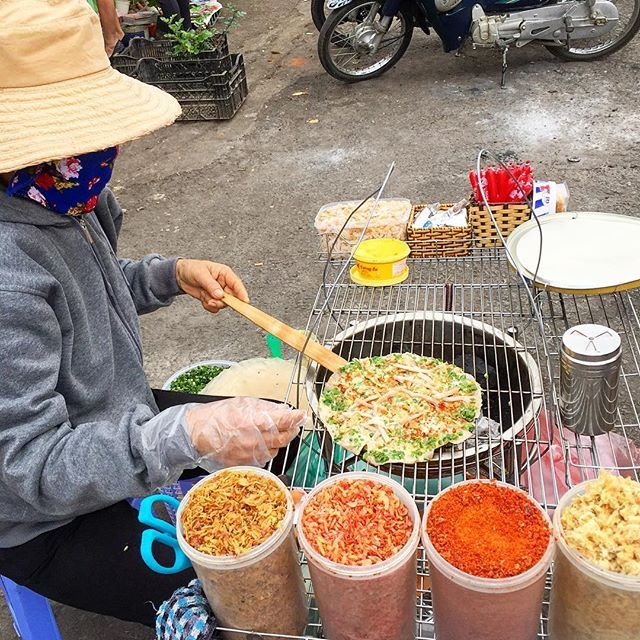 One of the best things we ate in Da Lat. Bánh xèo (I think) - a grilled crepe topped with dried shrimp, crispy fried shallots, green onions, chili sauce, and other delicious things, made to order and rolled up for easy portability.  I could eat 8. #streetfood #dalat #vietnam #banhxeo #travel #southeastasia
