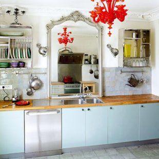 Cuisine installée dans un ancien salon mouluré. Devant l\'évier, un ancien miroir, la vaisselle est rangée dans des égouttoirs indiens (Le Monde Sauvage) et l\'en est éclairé par un lustre en verre rouge et deux appliques Jieldé sur chaque côté du miroir